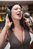 Woman singing with her hands on her headphone