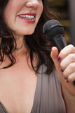 Close up of beautiful woman singing into a microphone