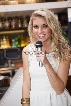 Blonde woman smiling while singing into a microphone