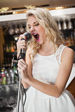 Beautiful young woman singing into a microphone