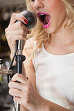 Close up of beautiful blonde singing into a microphone