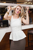 Charming blonde woman dancing holding her hair