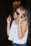 Pretty blonde in sunglasses listening to music and singing
