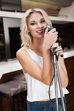 Smiling blonde girl singing with a microphone