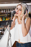 Pretty blonde with headphone singing into microphone