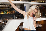 Blonde woman singing and dancing with hand up