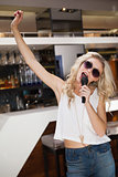 Woman in sunglasses singing and dancing with hand up