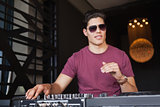 Cool dj in sunglasses working on a sound mixing desk