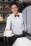 Young barista offering cup of coffee smiling at camera