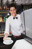 Barista offering cup of coffee smiling at camera