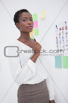 Thoughtful designer standing and holding pen