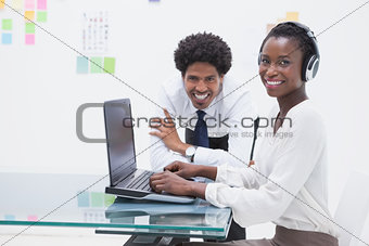 Smiling business coworkers using laptop