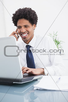 Smiling businessman on the phone and using laptop