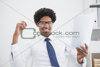 Smiling businessman holding paper and pen