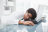 Businessman with glasses sleeping on laptop