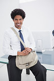 Smiling businessman with shoulder bag