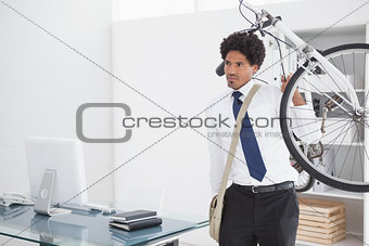Attractive businessman carrying his bike