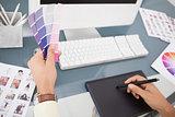 Designer working at desk using digitizer and colour sample