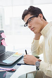 Designer with glasses thinking and using digitizer