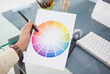 Designer working at desk using a colour wheel