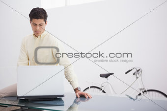Thoughtful causal businessman using laptop