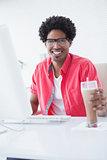 Smiling casual businessman holding glass of milkshake