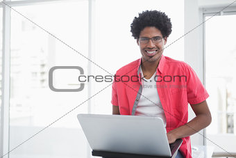 Casual businessman smiling and using laptop
