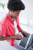 Happy casual businessman using laptop