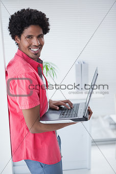 Casual businessman standing and using laptop