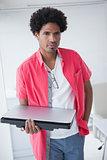 Portarit of a serious businessman holding laptop