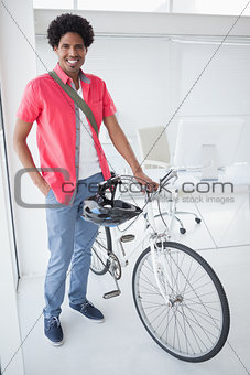 Smiling businessman standing with his bike