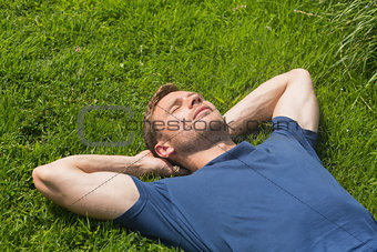 Casual man lying on the grass