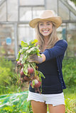 Happy blonde showing home grown vegetables