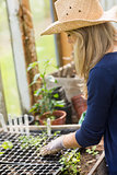 Pretty blonde gardening in greenhouse