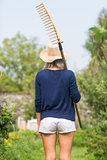 Gardening blonde holding a rake