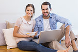 Cute couple sitting on floor using laptop