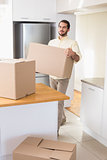 Young man unpacking boxes in kitchen
