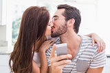 Young man using smartphone while girlfriend kisses him