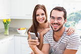Young couple smiling at the camera man holding smartphone