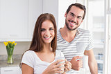Young couple smiling at the camera having coffee