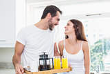 Young couple with breakfast on tray