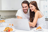Young couple using laptop at breakfast
