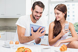Young couple using tablet at breakfast