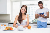 Young couple using technology at breakfast