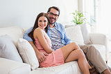 Young couple smiling at camera on couch