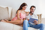 Hipster couple using tablet on couch