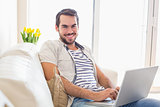 Hipster man using laptop on couch