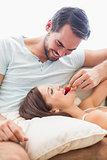 Man feeding his girlfriend a strawberry