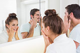 Young couple putting on face cream