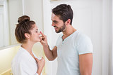 Young man putting cream on girlfriends nose